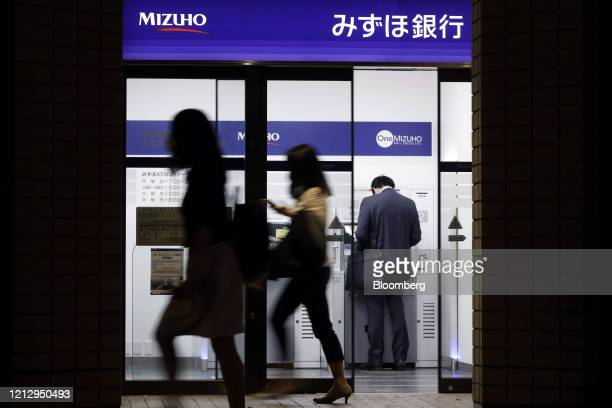 Pedestrians walk past a customer using an automated teller machine at a branch of Mizuho Bank Ltd., a unit of Mizuho Financial Group Inc. , at night...