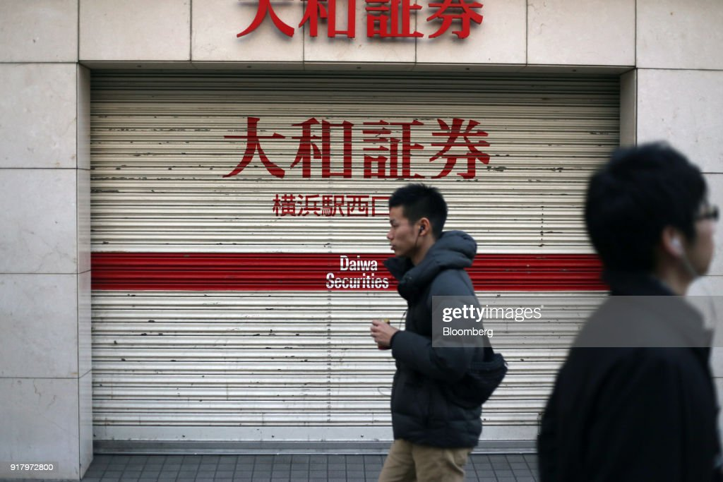 Pedestrians walk past a Daiwa Securities Co. branch in Yokohama, Japan, on Saturday, Feb. 3, 2018. Japans economy expanded for an eighth quarter, with its gross domestic product (GDP) grew at an annualized rate of 0.5 percent in the three months ended Dec. 31, but the pace of growth fell sharply and missed expectations. Photographer: Takaaki Iwabu/Bloomberg via Getty Images