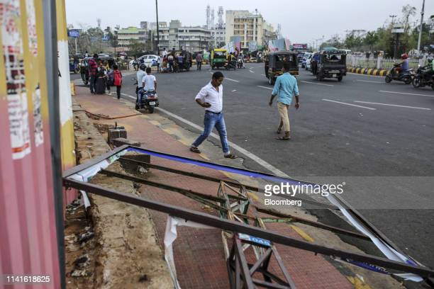 Pedestrians walk past a damaged adverting billboard after Cyclone Fani passes in Bhubaneshwar Odisha India on Sunday May 5 2019 Authorities launched...