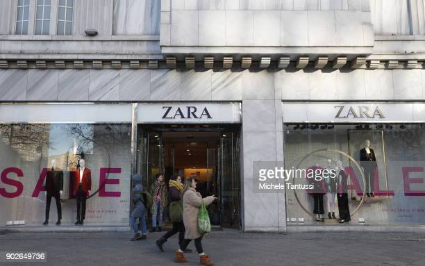 Pedestrians walk past a display window offering post-Christmas sales outside a Zara clothing store on January 8, 2018 in Berlin, Germany. Many German...