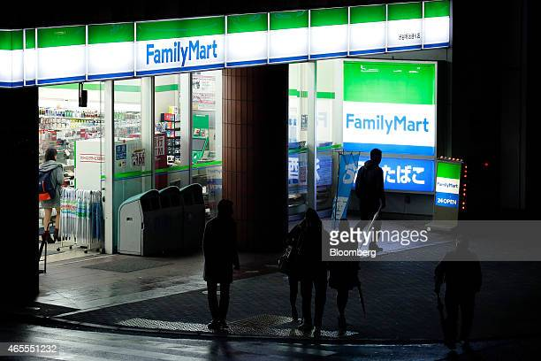 Pedestrians walk past a FamilyMart Co convenience store at night in Tokyo Japan on Saturday March 7 2015 FamilyMart and Uny Group Holdings Co are in...