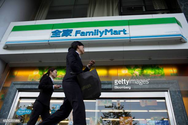 Pedestrians walk past a FamilyMart Co convenience store in the Tianhe district of Guangzhou Guangdong province China on Monday Nov 25 2013 China is...