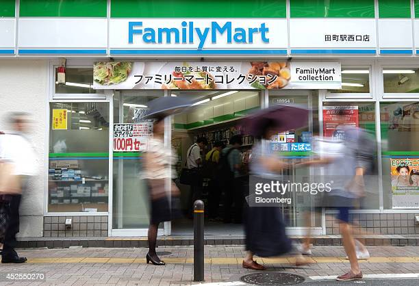 Pedestrians walk past a FamilyMart Co convenience store in Tokyo Japan on Wednesday July 23 2014 Japan suspended food imports from Shanghai Husi Food...