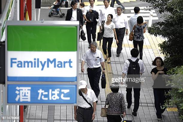 Pedestrians walk past a FamilyMart convenient store in Kawasaki Kanagawa Prefecture Japan on Thursday Sept 29 2016 The Bank of Japan will release the...