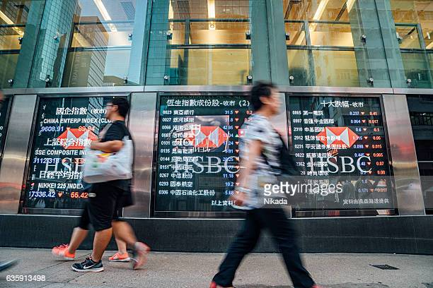 Pedestrians walk past a financial display board im Hongkong