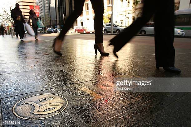 Pedestrians walk past a footpath plaque commemorating Rolf Harris on St Georges Terrace on July 2 2014 in Perth Australia Harris has been found...