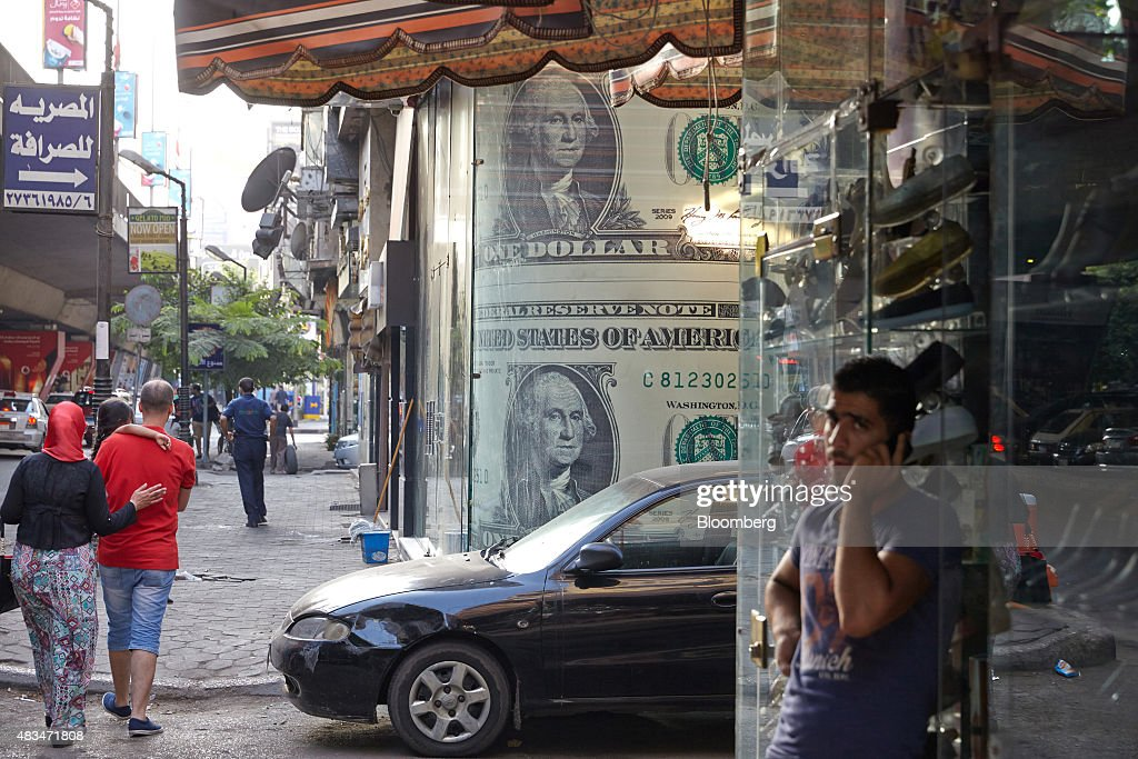 Pedestrians walk past a foreign currency exchange bureau decorated with U.S. one dollar banknotes in Cairo, Egypt, on Friday, Aug. 7, 2015. The Suez canal extension and other construction projects have boosted the economy, which grew above 4 percent in the nine months to March for the first time since 2010. Photographer: Shawn Baldwin/Bloomberg via Getty Images