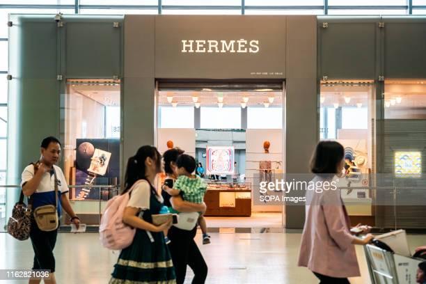 Pedestrians walk past a French high fashion luxury goods manufacturer Hermès store in Shanghai Hongqiao International Airport