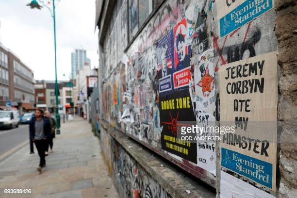 TOPSHOT Pedestrians walk past a general election themed poster reading 'Jeremy Corbyn ate my Hamster' as she walks on brick Lane east London on June...