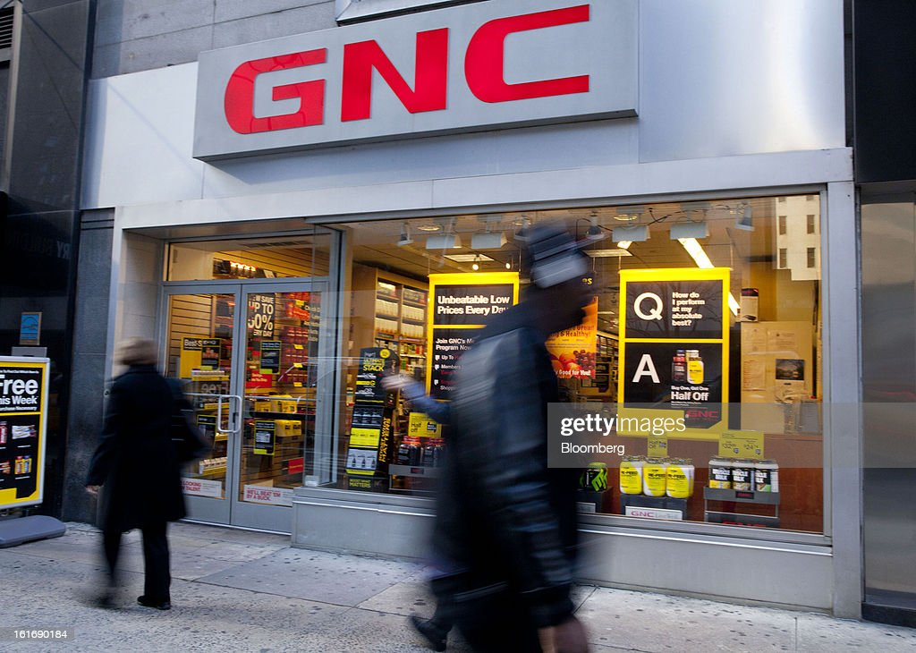 Pedestrians walk past a GNC Holdings Inc. store in New York, U.S., on Thursday, Feb. 14, 2013. GNC Holdings Inc., a retailer of health and wellness products, reported revenue increases of 10.9% in the fourth quarter and 17.3% for the full year. Photographer: Jin Lee/Bloomberg via Getty Images
