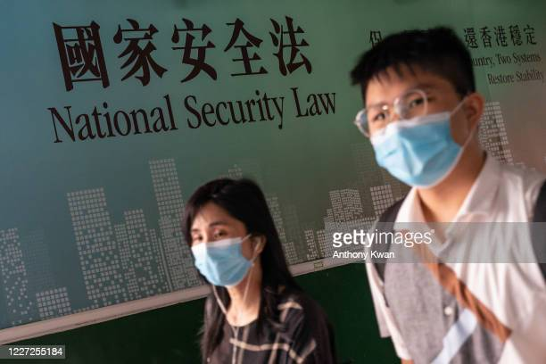 Pedestrians walk past a government-sponsored advertisement promoting a new national security law on July 15, 2020 in Hong Kong, China. Donald Trump...