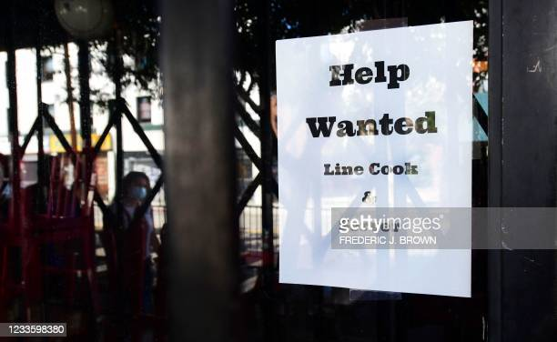 """Pedestrians walk past a """"Help Wanted"""" sign posted at restaurant looking for line cooks and servers on June 22, 2021 in Los Angeles, California. -..."""