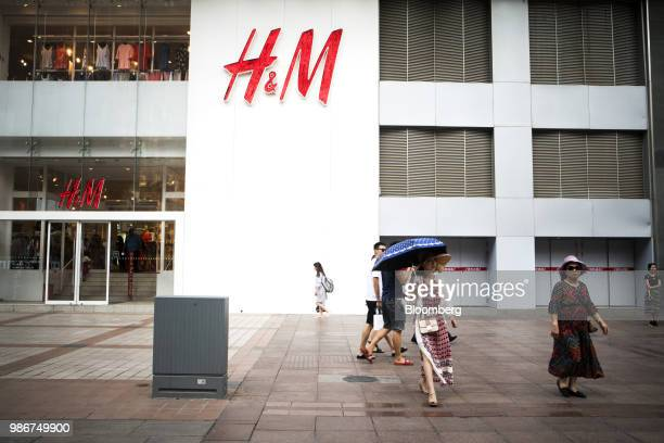 Pedestrians walk past a Hennes Mauritz AB store on Wangfujing Street in Beijing China on Wednesday June 27 2018 Consumer sentiment in China remains...