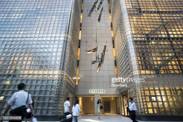 Pedestrians walk past a Hermes International SCA store at night in the Ginza area of Tokyo Japan on Tuesday Aug 21 2018 Japan is scheduled to release...