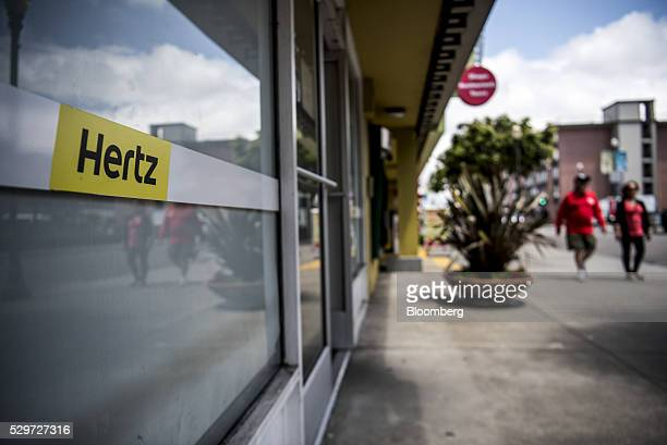 Pedestrians walk past a Hertz Global Holdings Inc car rental location in San Francisco California US on Thursday May 5 2016 Hertz is scheduled to...