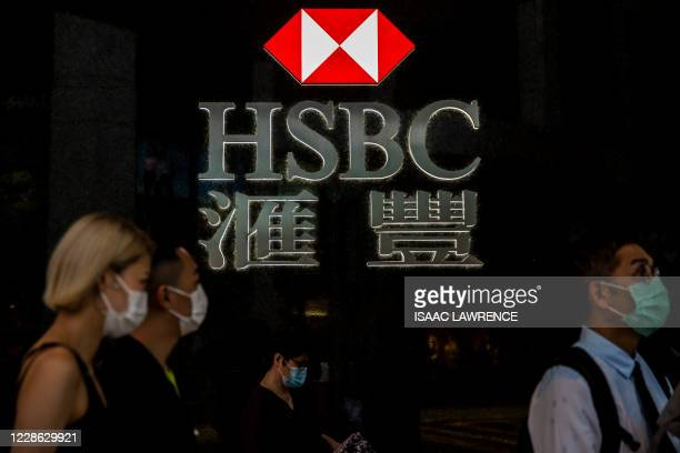 Pedestrians walk past a HSBC logo in Hong Kong on September 21, 2020. - Shares in banking giant HSBC plunged to a 25-year low September 21 on fears...