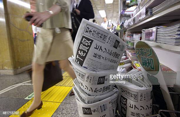Pedestrians walk past a kiosk selling the Nikkei newspaper in Tokyo Japan on Friday July 24 2015 After almost six decades of stewardship of one of...