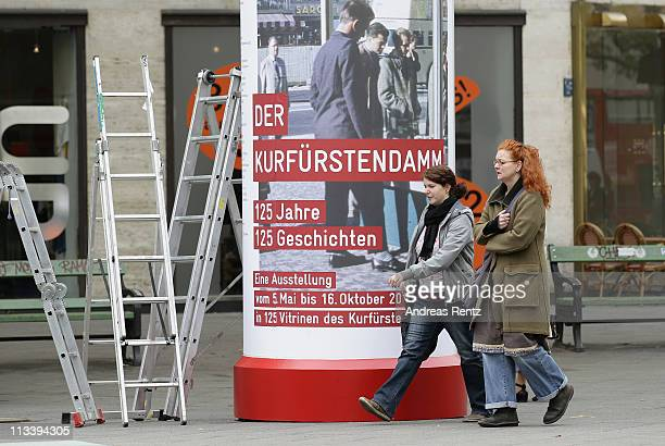 Pedestrians walk past a large poster on a advertising column that shows the '125 years Kurfuerstendamm anniversary' at the Kurfuerstendamm on May 2...