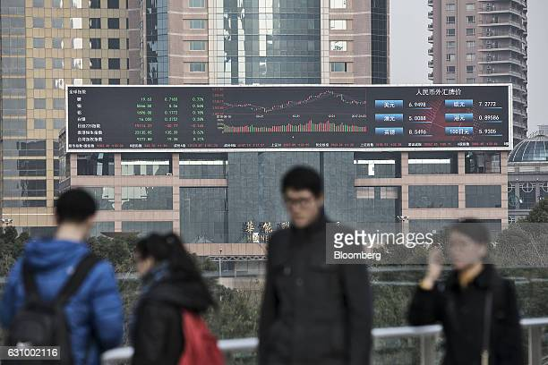 Pedestrians walk past a large screen showing financial data in Shanghai China on Wednesday Jan 4 2017 After defying skeptics with solid growth last...