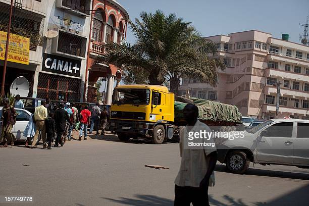 Pedestrians walk past a loaded truck and a Canal Plus logo on a building on a main street in central Lubumbashi Democratic Republic of Congo on...