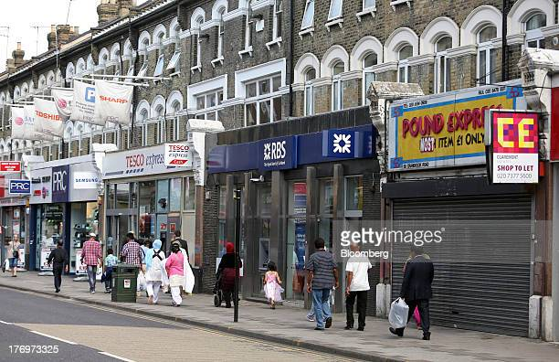 Pedestrians walk past a local branch of the Royal Bank of Scotland Group Plc located on Cranbrook Road in Ilford, U.K., on Tuesday, Aug 20, 2013. W&G...