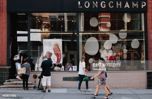Pedestrians walk past a Longchamp Co store in the SoHo neighborhood of New York US on Wednesday June 18 2014 The Bloomberg Consumer Comfort Index a...