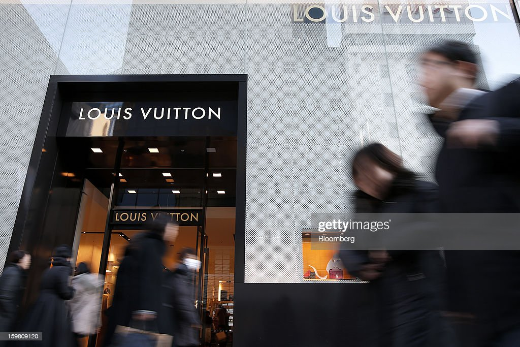 Pedestrians walk past a Louis Vuitton store, operated by LVMH Moet Hennessy Louis Vuitton SA, in the Ginza district of Tokyo, Japan, on Sunday, Jan. 20, 2013. Japan's consumer prices excluding fresh food, a benchmark monitored by the central bank, haven't advanced 2 percent for any year since 1997, when a national sales tax was increased. Photographer: Kiyoshi Ota/Bloomberg via Getty Images