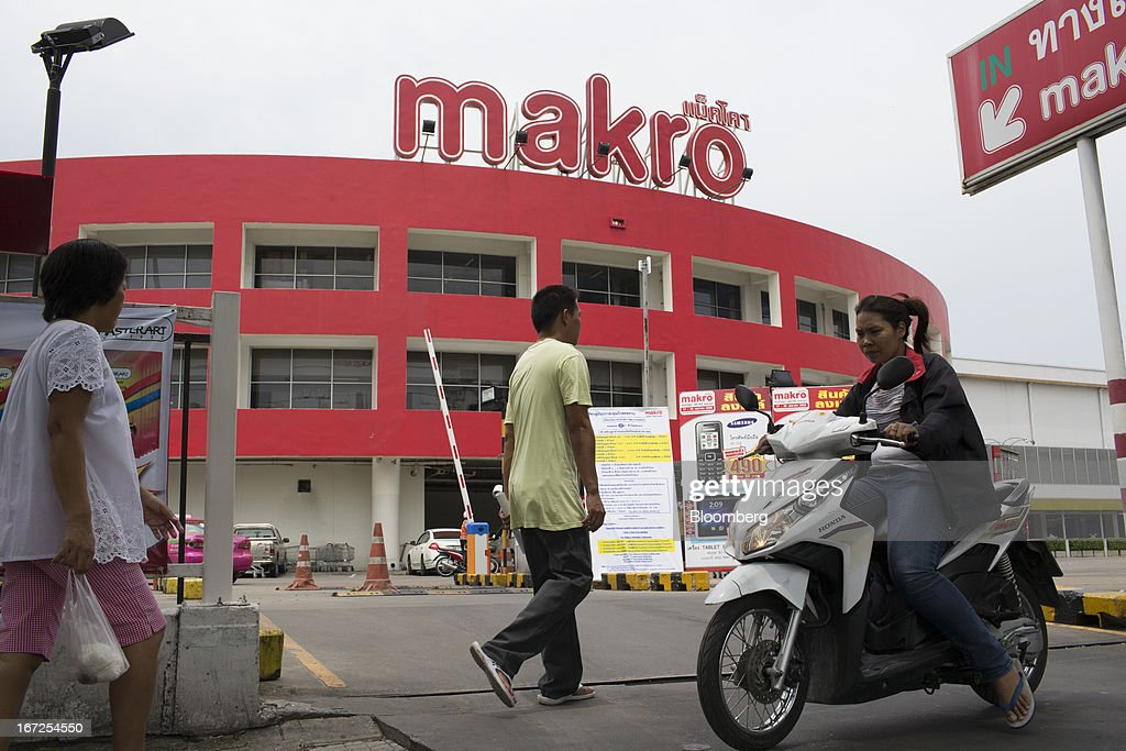 Pedestrians walk past a Makro store, operated by Siam Makro Pcl, in Bangkok, Thailand, on Tuesday, April 23, 2013. Billionaire Dhanin Chearavanont's CP All Pcl, Thailand's 7-Eleven chain, offered to pay about $6.6 billion for discount retailer Siam Makro Pcl in the biggest takeover announced in Asia this year. Photographer: Brent Lewin/Bloomberg via Getty Images