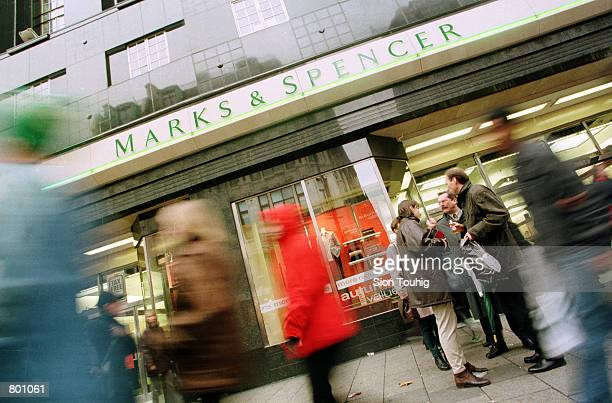 Pedestrians walk past a Marks and Spencers store April 12 2001 on London's Oxford Street Stormy days still lie ahead for Marks and Spencers as their...