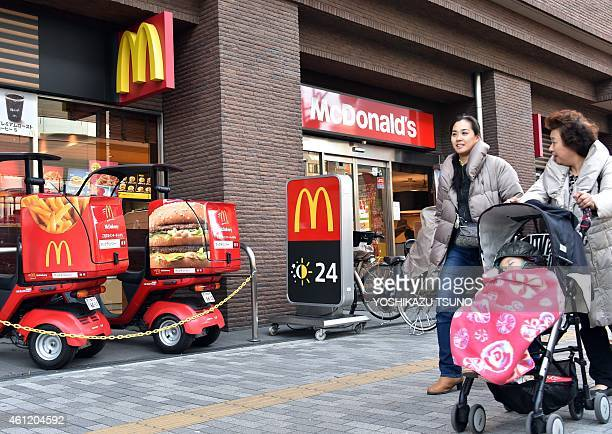 Pedestrians walk past a McDonald's fastfood restaurant in Tokyo on January 9 2015 A Japanese woman discovered fragments of 'dental material' in a...