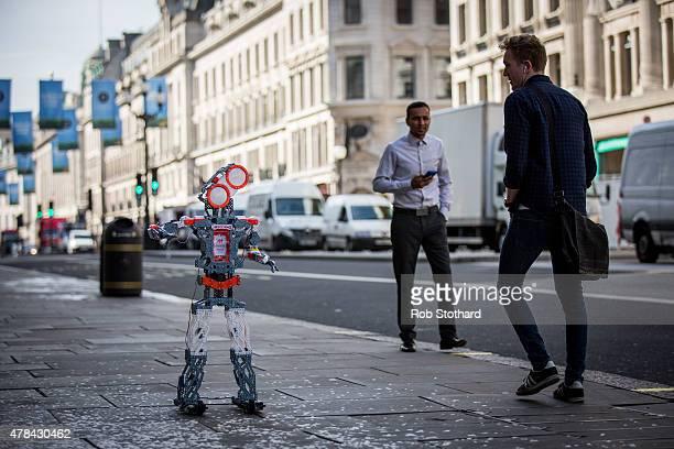 Pedestrians walk past a 'Meccanoid G15 KS' robot outside Hamleys on Regent Street on June 25 2015 in London England The robot which is preprogrammed...