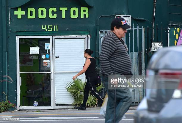 Pedestrians walk past a medical marijuana dispensary in Hollywood California on November 1 2016 ahead of next week's general elections where...