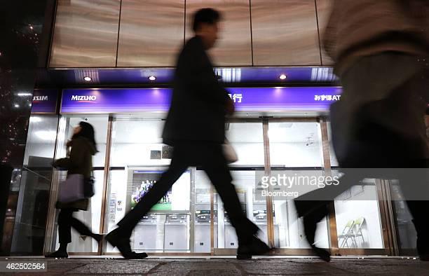 Pedestrians walk past a Mizuho Bank Ltd branch in Tokyo Japan on Thursday Jan 29 2015 Mizuho Financial Group Inc Japan's third largest bank is...