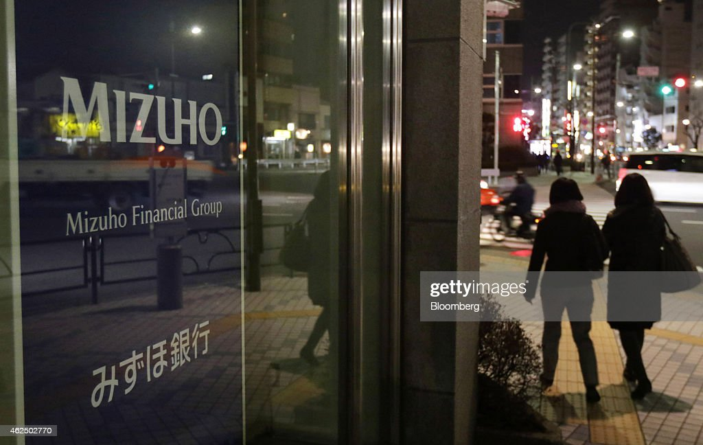 Pedestrians walk past a Mizuho Bank Ltd. branch in Tokyo, Japan, on Thursday, Jan. 29, 2015. Mizuho Financial Group Inc., Japan's third largest bank, is scheduled to report third-quarter earnings on Jan. 30. Photographer: Tomohiro Ohsumi/Bloomberg via Getty Images