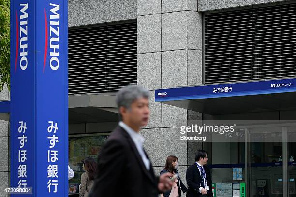 Pedestrians walk past a Mizuho Bank Ltd branch in Tokyo Japan on Tuesday May 12 2015 Mizuho Financial Group Inc is scheduled to release their...