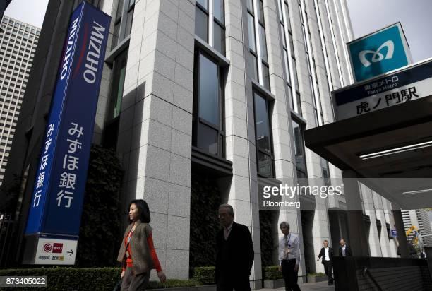 Pedestrians walk past a Mizuho Bank Ltd branch in Tokyo Japan on Friday Nov 10 2017 Mizuho Financial Group Japan's third largest lender is scheduled...