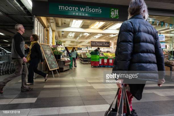 Pedestrians walk past a Moore Wilson Co supermarket in Wellington New Zealand on Wednesday July 18 2018 New Zealand inflation picked up in the second...