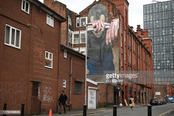 Pedestrians walk past a mural painted as part of the Cities of Hope festival in 2016 and highlighting the effects of mental health, in Ancoats,...