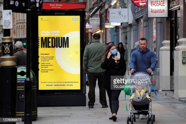 Pedestrians walk past a NHS sign displaying guidelines during the novel coronavirus COVID-19 pandemic, on a bus-stop shelter in the West End of...