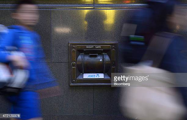 Pedestrians walk past a night safe at an Australia New Zealand Banking Group Ltd branch in Melbourne Australia on Friday May 1 2015 ANZ Australia's...