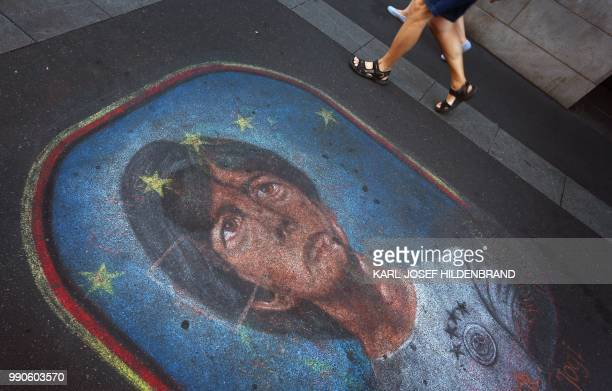 TOPSHOT Pedestrians walk past a pavement painting that depicts the head coach of Germany's national football team Joachim Loew on July 3 2018 in...