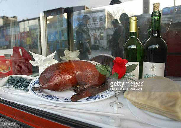 Pedestrians walk past a Peking Duck meal displayed in front of a Beijing restaurant 03 February 2004 The outbreak of bird flu may be depressing the...