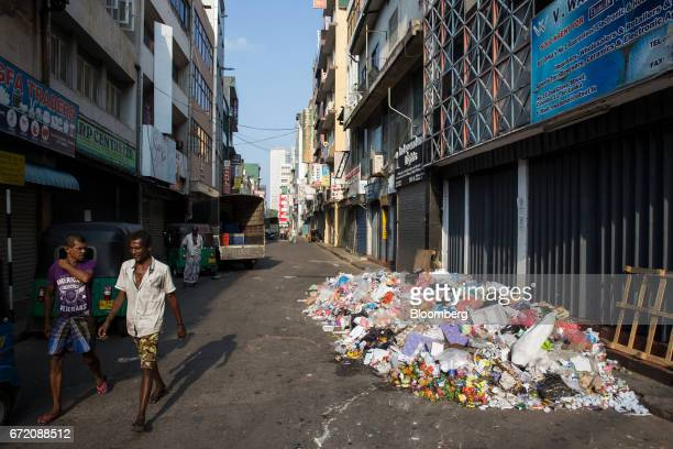 Pedestrians walk past a pile of trash in the Pettah neighborhood of Colombo Sri Lanka on Thursday April 20 2017 The Central Bank of Sri Lanka is...