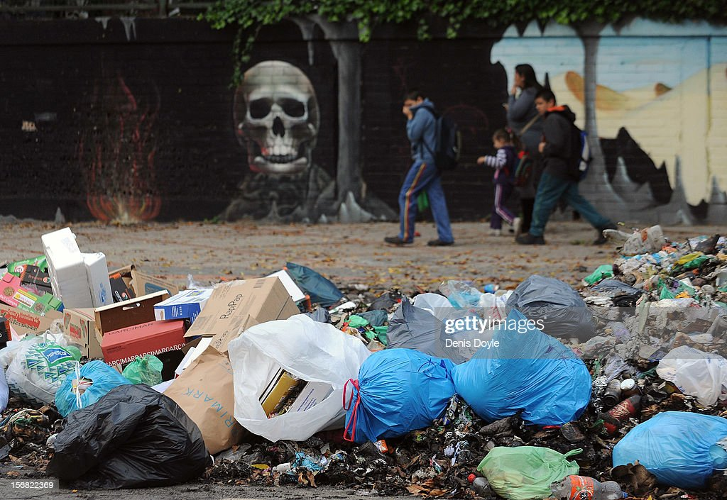 Pedestrians walk past a pile of uncollected garbage during the 21st day of the garbage collectors strike on November 22, 2012 in Jerez de la Frontera, Spain. The garbage collectors will vote today on a compromise deal which saves the 123 jobs due to be cut in favour of reductions in salaries.