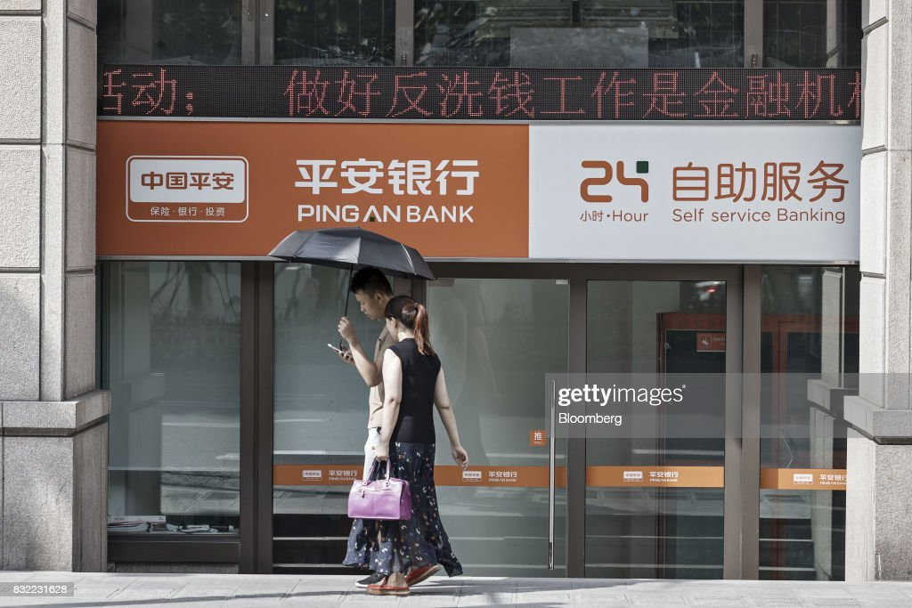 Pedestrians walk past a Ping An Bank Co. branch, a unit of Ping An Insurance Group Co., in Shanghai, China, on Wednesday, Aug. 13, 2017. Ping An Insurance Group is scheduled to release half year results on Aug. 17. Photographer: Qilai Shen/Bloomberg via Getty Images