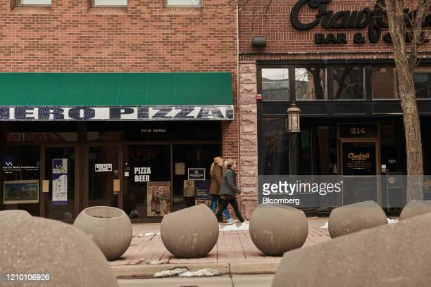 Pedestrians walk past a pizza store in downtown Sioux Falls South Dakota US on Wednesday April 15 2020 South Dakota Governor Kristi Noem has argued...