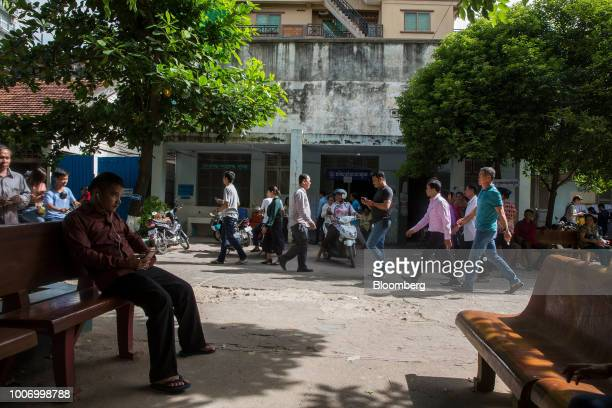 Pedestrians walk past a polling station in Phnom Penh Cambodia on Sunday July 29 2018 As Cambodians vote on Sunday a win is all but assured for...