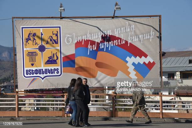 Pedestrians walk past a poster bearing a flag of Nagorno-Karabakh in the region's capital Stepanakert on November 24 after Armenia and Azerbaijan...