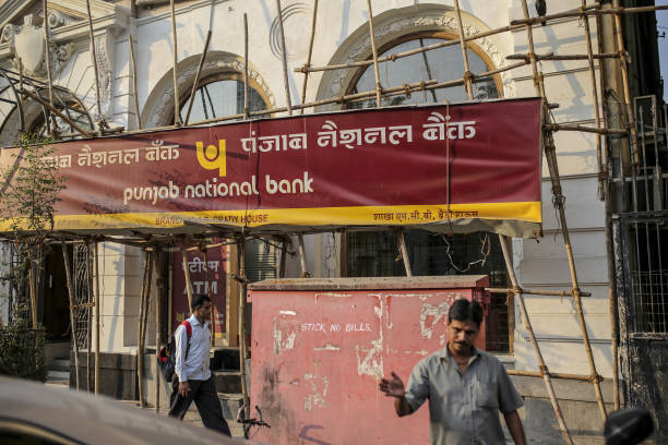 Pedestrians walk past a Punjab National Bank branch in Mumbai India on Wednesday Feb 14 2018 PNB one of India`s biggest banks has accused...