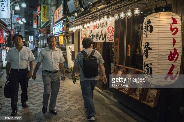 Pedestrians walk past a ramen noodle shop in the Ikebukuro district of Tokyo, Japan, on Aug. 8, 2019. Japans economy grew more than expected in the...